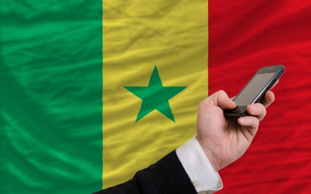 telecommuniation: man holding cell phone in front national flag of senegal symbolizing mobile communication and telecommunication