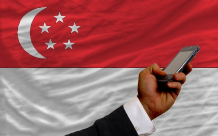 telecommuniation: man holding cell phone in front national flag of singapore symbolizing mobile communication and telecommunication Editorial