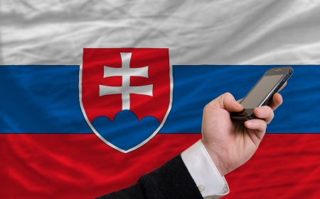 telecommuniation: man holding cell phone in front national flag of slovakia symbolizing mobile communication and telecommunication