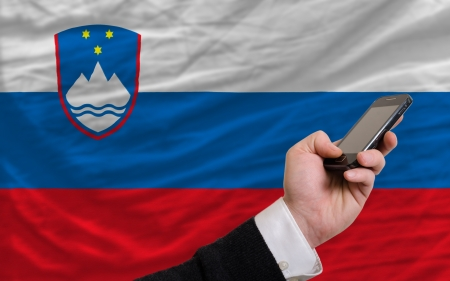 man holding cell phone in front national flag of slovenia symbolizing mobile communication and telecommunication Stock Photo