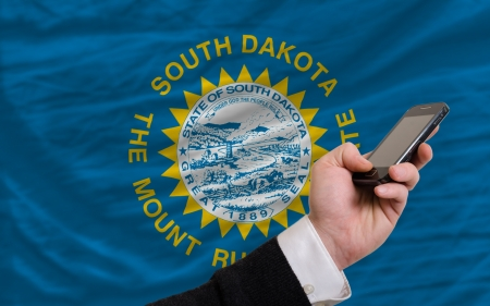 telecommuniation: man holding cell phone in front flag of us state of south dakota symbolizing mobile communication and telecommunication