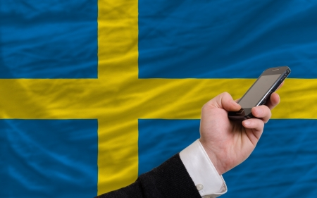 telecommuniation: man holding cell phone in front national flag of sweden symbolizing mobile communication and telecommunication