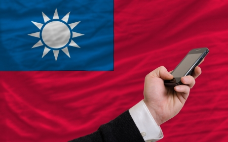 telecommuniation: man holding cell phone in front national flag of taiwan symbolizing mobile communication and telecommunication