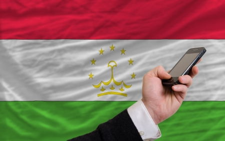 telecommuniation: man holding cell phone in front national flag of tajikistan symbolizing mobile communication and telecommunication Stock Photo