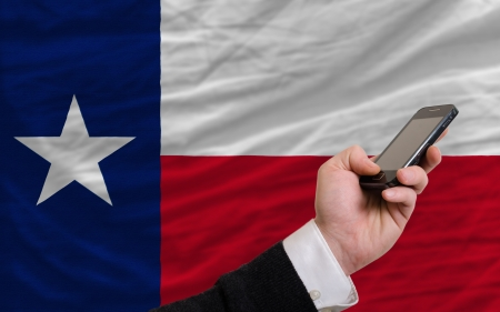 man holding cell phone in front flag of us state of texas symbolizing mobile communication and telecommunication