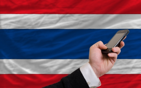 man holding cell phone in front national flag of thailand symbolizing mobile communication and telecommunication