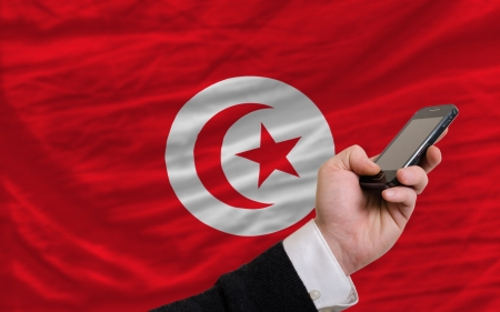man holding cell phone in front national flag of tunisia symbolizing mobile communication and telecommunication
