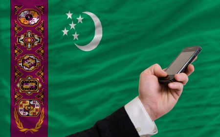 telecommuniation: man holding cell phone in front national flag of turkmenistan symbolizing mobile communication and telecommunication