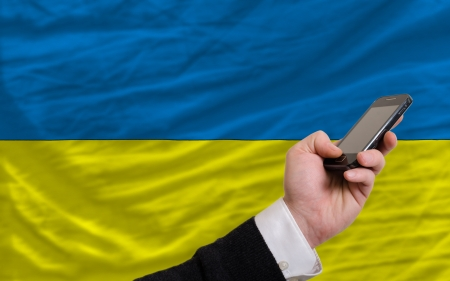 man holding cell phone in front national flag of ukraine symbolizing mobile communication and telecommunication