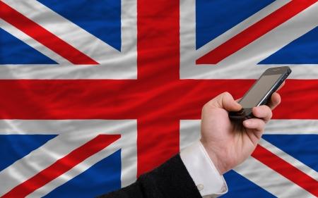 man holding cell phone in front national flag of uk symbolizing mobile communication and telecommunication Stock Photo