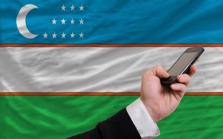 telecommuniation: man holding cell phone in front national flag of uzbekistan symbolizing mobile communication and telecommunication