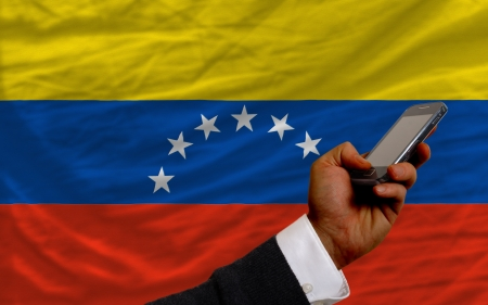 telecommuniation: man holding cell phone in front national flag of venezuela symbolizing mobile communication and telecommunication