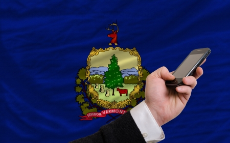 telecommuniation: man holding cell phone in front flag of us state of vermont symbolizing mobile communication and telecommunication Stock Photo