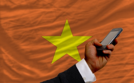 telecommuniation: man holding cell phone in front national flag of vietnam symbolizing mobile communication and telecommunication Stock Photo