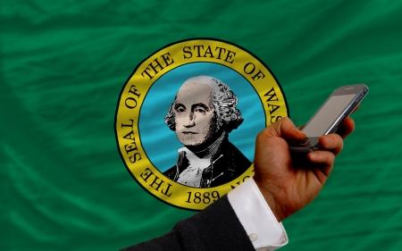 man holding cell phone in front flag of us state of washington symbolizing mobile communication and telecommunication Stock Photo