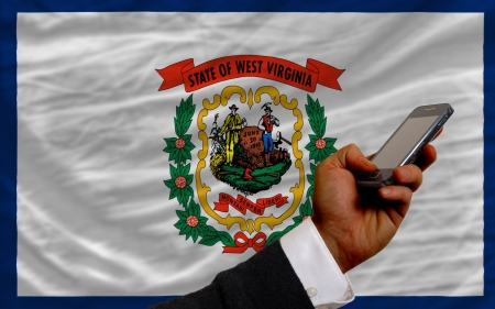 telecommuniation: man holding cell phone in front flag of us state of west virginia symbolizing mobile communication and telecommunication