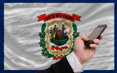man holding cell phone in front flag of us state of west virginia symbolizing mobile communication and telecommunication