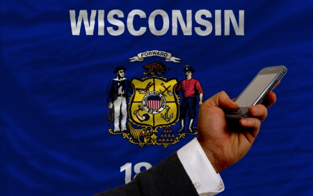 telecommuniation: man holding cell phone in front flag of us state of wisconsin symbolizing mobile communication and telecommunication
