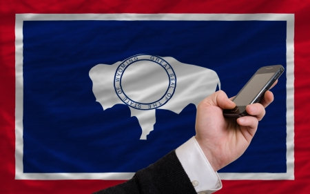 telecommuniation: man holding cell phone in front flag of us state of wyoming symbolizing mobile communication and telecommunication