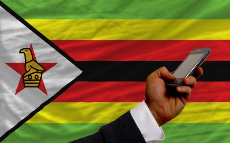 man holding cell phone in front national flag of zimbabwe symbolizing mobile communication and telecommunication Stock Photo - 17996186