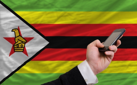 man holding cell phone in front national flag of zimbabwe symbolizing mobile communication and telecommunication Stock Photo - 17996166