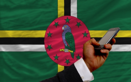 man holding cell phone in front national flag of dominica symbolizing mobile communication and telecommunication Stock Photo