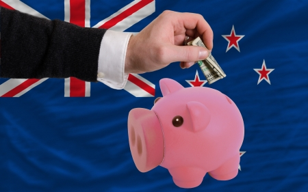 foreign national: Man putting dollar into piggy rich bank national flag of new zealand in foreign currency because of inflation