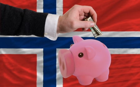 foreign national: Man putting dollar into piggy rich bank national flag of norway in foreign currency because of inflation Stock Photo