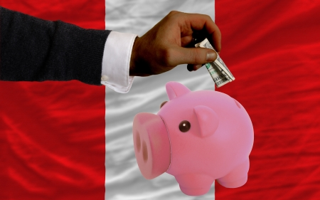 Man putting dollar into piggy rich bank national flag of peru in foreign currency because of inflation photo