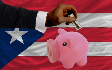foreign national: Man putting dollar into piggy rich bank national flag of puertorico in foreign currency because of inflation Stock Photo