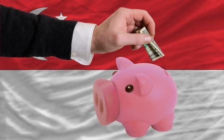 foreign national: Man putting dollar into piggy rich bank national flag of singapore in foreign currency because of inflation
