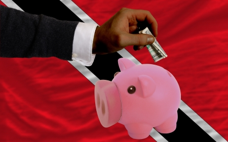 national flag trinidad and tobago: Man putting dollar into piggy rich bank national flag of trinidad tobago in foreign currency because of inflation Stock Photo
