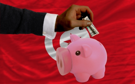 foreign national: Man putting dollar into piggy rich bank national flag of tunisia in foreign currency because of inflation Stock Photo