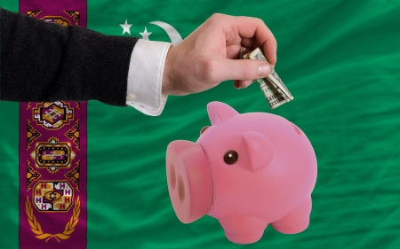 foreign national: Man putting dollar into piggy rich bank national flag of turkmenistan in foreign currency because of inflation