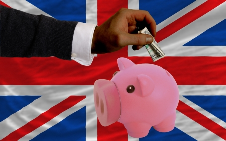 Man putting dollar into piggy rich bank national flag of uk in foreign currency because of inflation photo