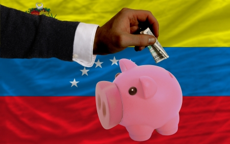 foreign national: Man putting dollar into piggy rich bank national flag of venezuela in foreign currency because of inflation Stock Photo