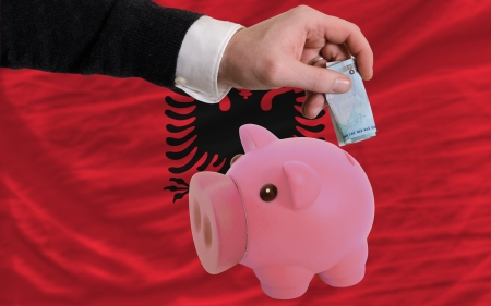 Man putting euro into piggy rich bank and national flag of albania in foreign currency because of insecurity and inflation photo
