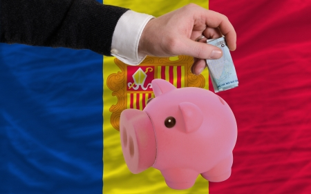 tourism in andorra: Man putting euro into piggy rich bank and national flag of andorra in foreign currency because of insecurity and inflation Stock Photo