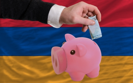 Man putting euro into piggy rich bank and national flag of armenia in foreign currency because of insecurity and inflation Stock Photo - 18039371
