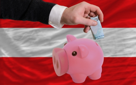 foreign national: Man putting euro into piggy rich bank and national flag of austria in foreign currency because of insecurity and inflation