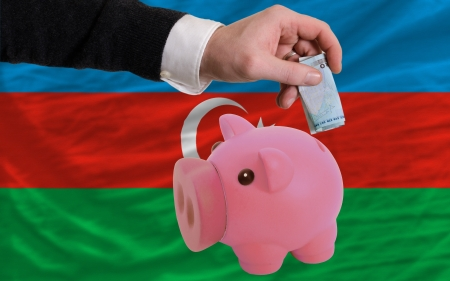 foreign national: Man putting euro into piggy rich bank and national flag of azerbaijan in foreign currency because of insecurity and inflation