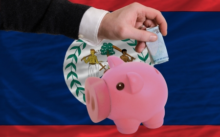 foreign national: Man putting euro into piggy rich bank and national flag of belize in foreign currency because of insecurity and inflation