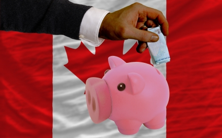 foreign national: Man putting euro into piggy rich bank and national flag of canada in foreign currency because of insecurity and inflation