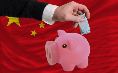 Man putting euro into piggy rich bank and national flag of china in foreign currency because of insecurity and inflation photo