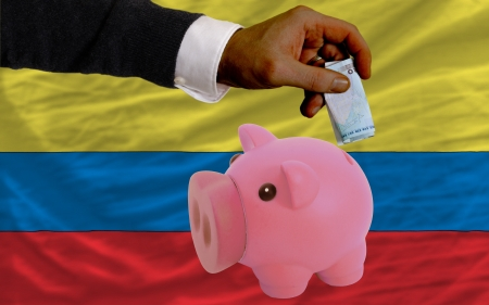 foreign national: Man putting euro into piggy rich bank and national flag of columbia in foreign currency because of insecurity and inflation Stock Photo