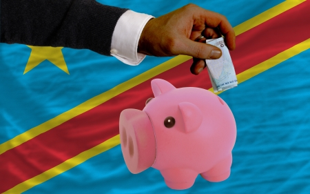 foreign national: Man putting euro into piggy rich bank and national flag of  congo in foreign currency because of insecurity and inflation