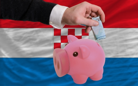 foreign national: Man putting euro into piggy rich bank and national flag of croatia in foreign currency because of insecurity and inflation