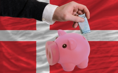 foreign national: Man putting euro into piggy rich bank and national flag of denmark in foreign currency because of insecurity and inflation Stock Photo