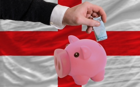 foreign national: Man putting euro into piggy rich bank and national flag of england in foreign currency because of insecurity and inflation