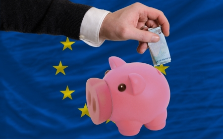 foreign national: Man putting euro into piggy rich bank and national flag of europe in foreign currency because of insecurity and inflation